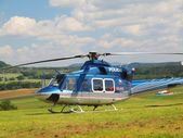 Police helicopter in action, propellers are turning and the m,achine is ready to fly. Blue sky in background — Stock Photo