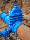 Old big drink water pipes joined with new blue valves and new blue joint members. Finished repaired piping waiting for covering by clay. Extreme kind of corrosion, metal corroded texture. — Stockfoto