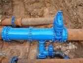 老喝大水管加入了新的蓝色阀门和新的蓝色联合会员。完成修复管道等覆盖粘土。极端的一种腐蚀,锈蚀的金属质感. — 图库照片