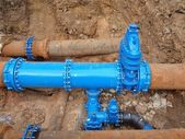 Old big drink water pipes joined with new blue valves and new blue joint members. Finished repaired piping waiting for covering by clay. Extreme kind of corrosion, metal corroded texture. — Foto de Stock