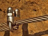Detail of chrome screws snap hooks and grommets at and of rope. Iron twisted rope fixed together by screws snap hooks. Detail of rope end anchored at sandstone rock — Stock Photo
