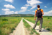 Man with a backpack on a country road. Man tourist. Leisure acti — Stock Photo