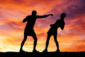 силуэты двух бойцов на фоне заката — Стоковое фото