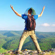 Man with a map on top of mountain — Stock Photo