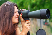 Positive girl who is watching in spotting scope. — Stock Photo