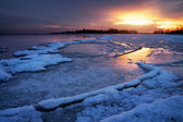 Winter landscape with frozen lake and sunset sky. — Stockfoto