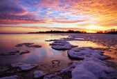 Winter landscape with lake and sunset fiery sky. — ストック写真