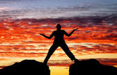 Silhouette of man on sunset fiery sky background — Stock Photo