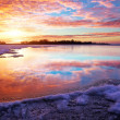 Winter landscape with lake and sunset fiery sky. — Stock Photo