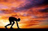 Silhouette of athlete in position to run on sunset background — Stock Photo