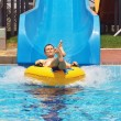 Men go down from water slide to swimming pool in aqua park. — Stock Photo #47659383