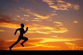 Silueta běžící muž na slunce ohnivé pozadí — Stock fotografie