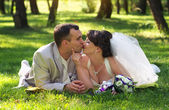 Beautiful newly married couple lying on grass at park and kissin — Stock Photo