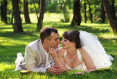 Beautiful newly married couple lying on grass at park and lookin — Stock Photo