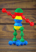 Toy robot made from toy plastic colorful details on wooden backg — Stockfoto