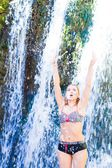 Young woman doing yoga exercise under waterfall — Stockfoto