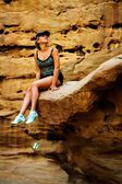 Girl sitting on a rock — Stock Photo