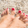 Womens sandy feet on beach — Stock Photo