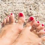 Womens sandy feet on beach — Stock Photo #35505037