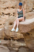 Girl sitting on a rock. — Stock Photo