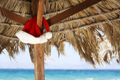 Hanging Santa Claus hat on palmy sunshade on beach — Stock Photo