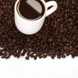Cup of coffee standing on coffee beans on white background — Stock Photo