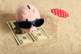 Summer piggy bank standing on towel from greenback hundred dollars with sunglasses on the beach and red parasol — Stock Photo