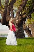 красивая беременная женщина расслабляющий в парке — Стоковое фото