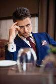 Successful businessman sitting at the table of the restaurant — Stock Photo