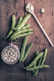 Broad Beans on a wooden Table with Jar, full of dry beans — Stock Photo