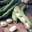 Broad Beans on a wooden Table with Jar, full of dry beans — Stock Photo #28930243
