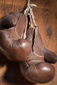 Old Boxing Gloves, hanging on wooden wall — Stock Photo