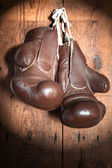Old Boxing Gloves, on wooden wall in the Spotlight — Stock Photo