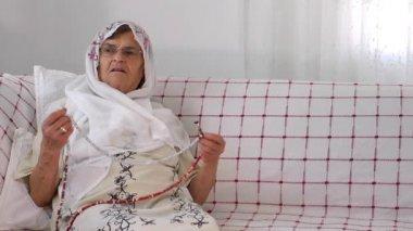 старая женщина молится с четок — Стоковое видео