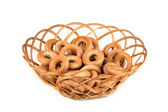 Tasty bagels in basket, isolated on white  — Stock Photo