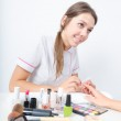 Mrs beautician dressed in professional attire doing his client a manicure. On the table is a lot of cosmetics. Brush, paint, rouge, eye shadow, lipstick. — Stock Photo