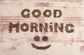 Large lettering good day on the wood of many aromatic beans, brown coffee — Stock Photo
