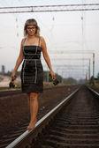 Jeune belle fille avec des lunettes sur le fond de la voie ferrée. — Photo