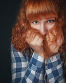 Frightened red-haired girl hides her face in her hair — Stock Photo