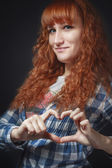 Red-haired girl shows heart — Stock Photo