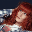 Red-haired girl shows emotion on a dark background — Stock Photo