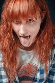 рыжеволосая девушка показывает язык — Стоковое фото