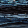 Many different denim jeans on a white background — Stock fotografie