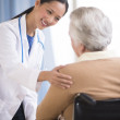 Doctor Consoling Senior Woman Sitting In Wheelchair — Stock Photo