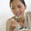 Stock Photo: Woman Looking Away While Eating Yoghurt And Olive