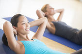 Woman Smiling While Doing Sit-Ups At Gym — Stock Photo