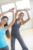 Happy Friends Doing Stretching Exercise At Gym — Stock Photo