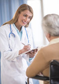 Doctor Writing On Clipboard While Communicating With Senior Woma — Stock Photo