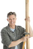 Happy Male Carpenter Holding Hammer And Wooden Plank — Stock Photo