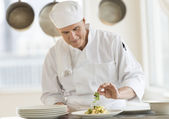 Chef Garnishing Dish In Commercial Kitchen — Stock Photo
